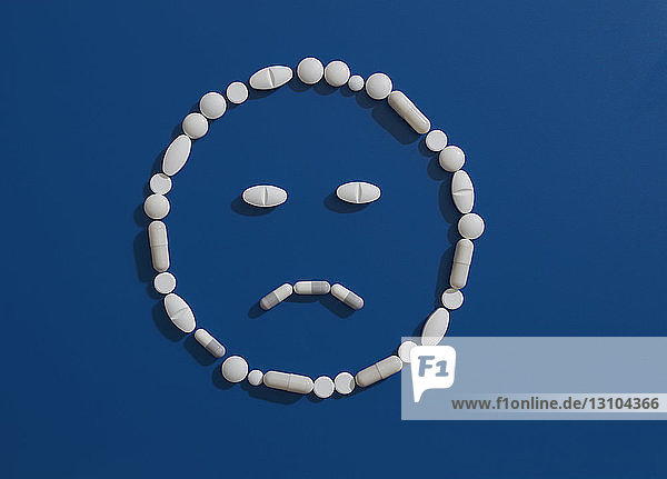 Pills forming frowning face on blue background