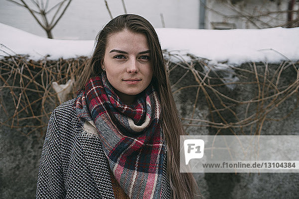 Portrait young woman in plaid scarf against snow covered wall