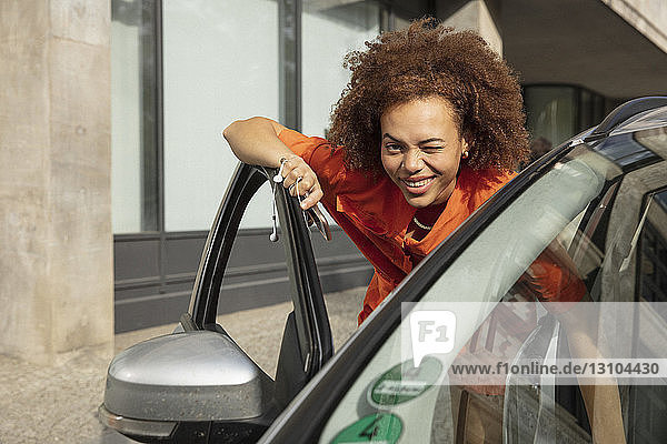 Portrait smiling  confident young woman winking  getting into car