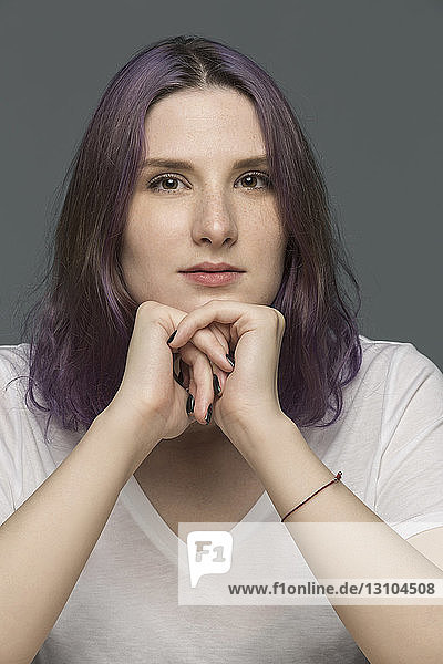 Portrait of a young woman with dyed hair and resting chin on hands against gray background