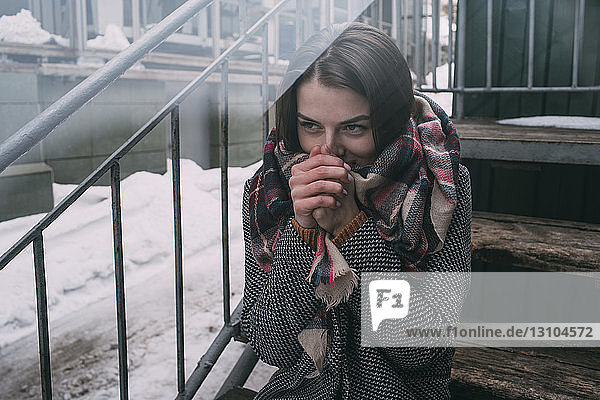Young woman warming hands on cold  winter stoop
