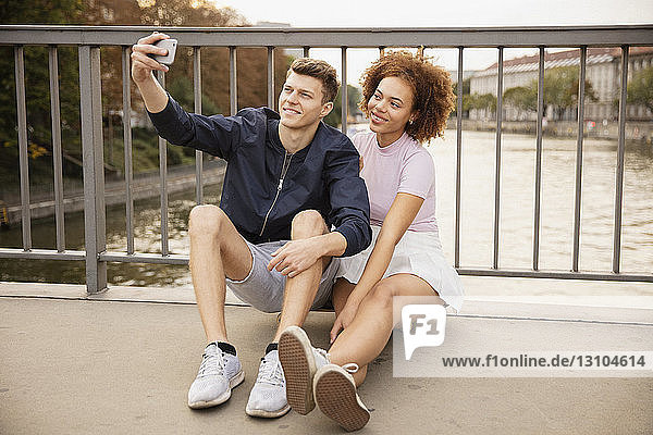 Young couple taking selfie with camera phone on urban bridge