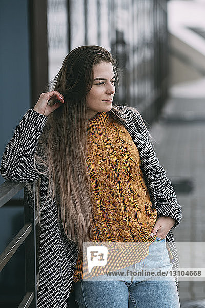 Young woman leaning against railing  looking away