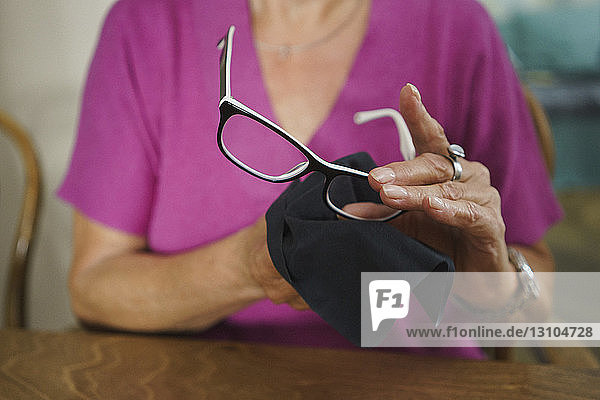 Senior woman cleaning eyeglasses