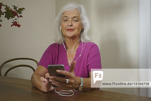 Senior woman listening to music with headphones and mp3 player
