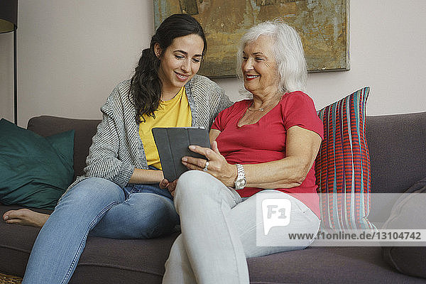 Senior mother and daughter using digital tablet on living room sofa