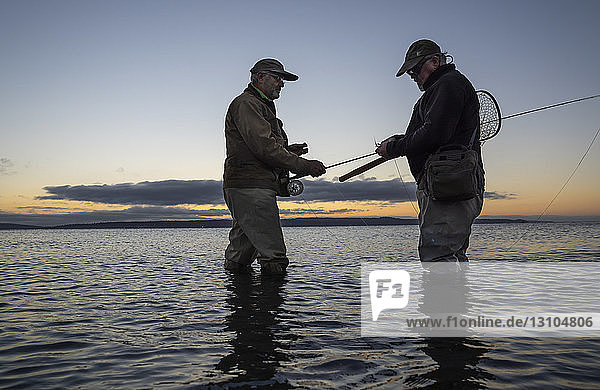 A male fly fisherman watches his guide work putting on a new fly to try for salmon or trout on a salt water beach at Fort Flagler State Park in northwest Washington State  USA
