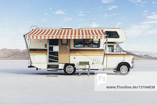 Vintage Dodge Sportsman RV mit gestreifter Überdachung auf Salt Flats geparkt