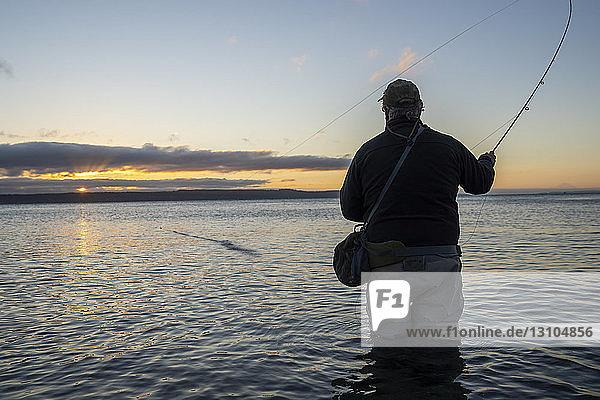 Die Silhouettenansicht eines Fliegenfischers,  der an einem Strand an der Nordwestküste der USA von einem Salzwasserstrand aus nach Lachsen und Cutthroat-Forellen der Searun-Küste wirft.