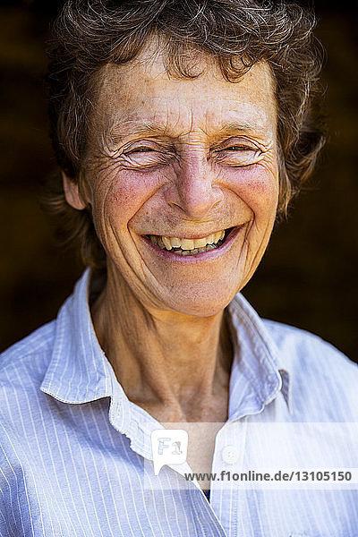 Porträt einer lächelnden älteren Frau  die in die Kamera schaut.