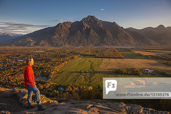 Man viewing scenery from the top of the Butte of farmlands and Pioneer Peak  South-central Alaska; Palmer  Alaska  United States of America
