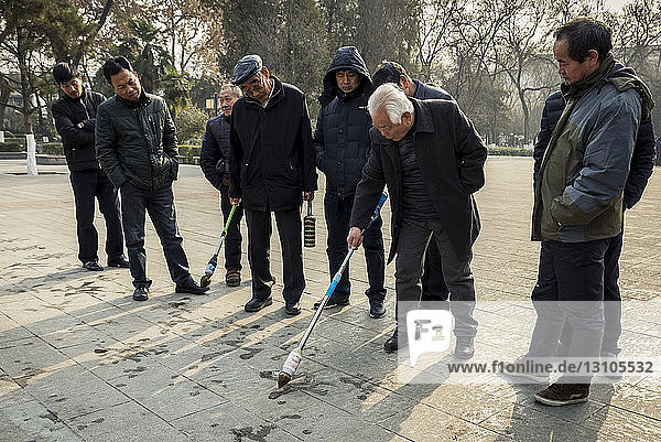 Chinese men practicing calligraphy in Revolution Park; Xian  Shaanxi Province  China