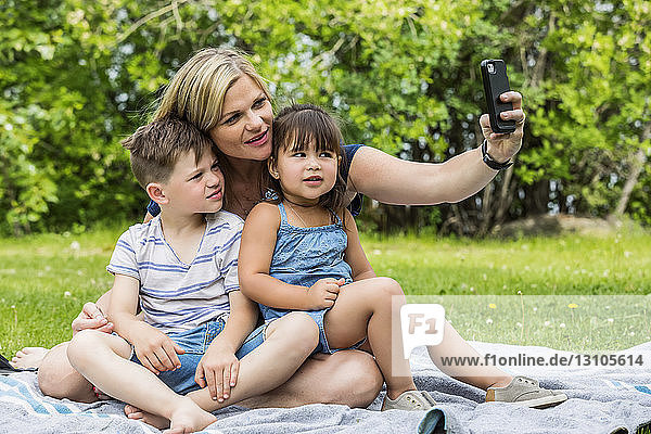 A young mother taking a self-portrait with her son and daughter in a park; Edmonton,  Alberta,  Canada
