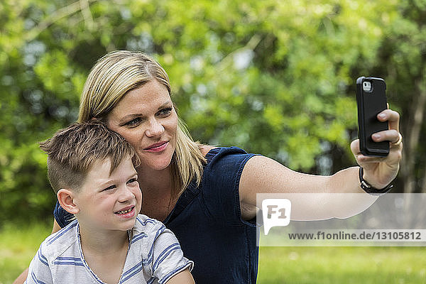 A young mother taking a self-portrait with her son in a park; Edmonton,  Alberta,  Canada