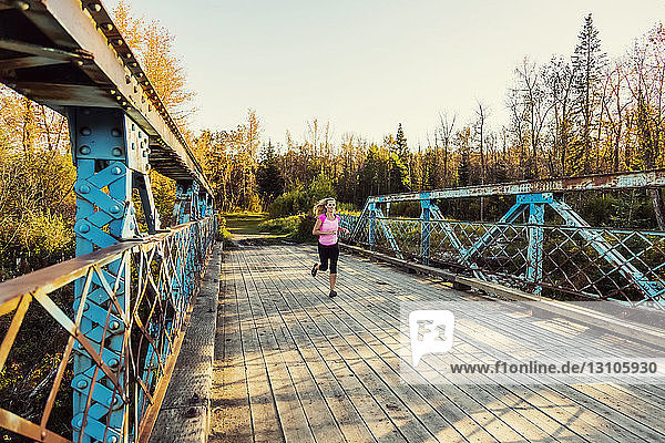 An attractive middle-aged woman running across a bridge while working out during a beautiful warm fall evening in a city park; Edmonton  Alberta  Canada