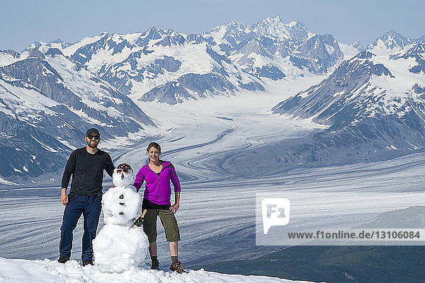A couple enjoy the sights and scenery of Kluane National Park and Reserve on a bright sunny day after building a snowman; Haines Junction  Yukon  Canada