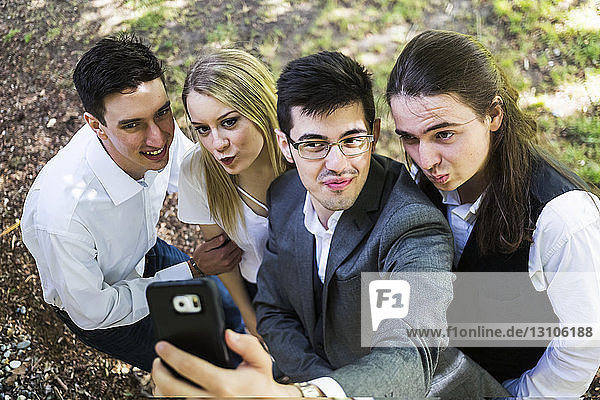 Four friends taking a silly self-portrait with a smart phone; Bothell  Washington  United States of America