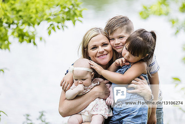 A young mother posing for the camera with her children while enjoying a family outing at a park on a warm sunny day; Edmonton,  Alberta,  Canada