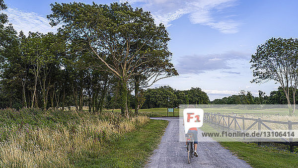A woman rides her bike down a road at Gleno Abbey Hotel and Golf Course; County Galway  Ireland