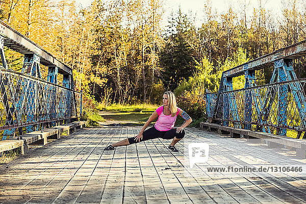 An attractive middle-aged woman pauses to stretch out her legs on a bridge during a run on a beautiful warm fall evening in a city park; Edmonton  Alberta  Canada