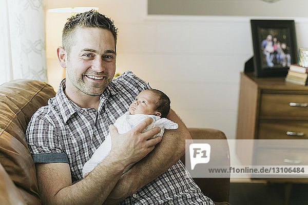 Portrait of a father holding his newborn baby; Surrey  British Columbia  Canada