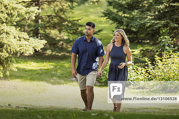 A mixed race married couple walking in a city park and holding hands as they enjoy time together on a warm sunny afternoon; Edmonton  Alberta  Canada