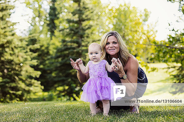 A mother teaching her baby daughter how to walk in a city park on a warm fall afternoon: Edmonton  Alberta  Canada