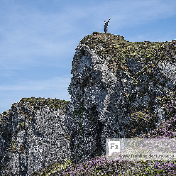 A man stands with arms raised at the edge of a rocky cliff looking out; Carrick  County Donegal  Ireland