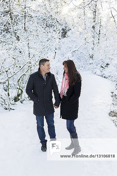 A couple standing together outside on a snowy trail; Surrey  British Columbia  Canada