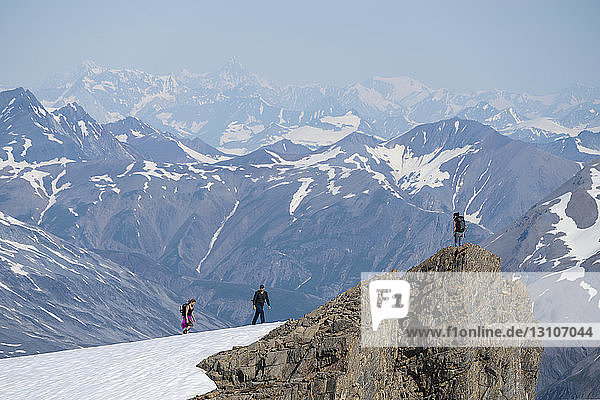 People walking on a mountain top with the massive mountains of Kluane National Park and Reserve looming in the distance; Haines Junction  Yukon  Canada