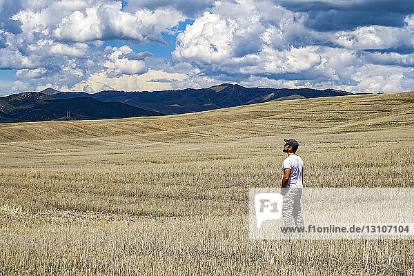 Standing in a vast farm field looking towards the mountains; Utah  United States of America