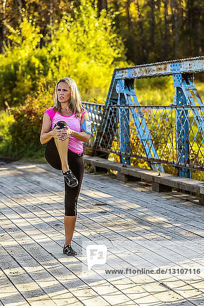 An attractive middle-aged woman listens to music on her smart phone and pauses to stretch on a bridge during a run on a beautiful warm fall evening in a city park; Edmonton  Alberta  Canada