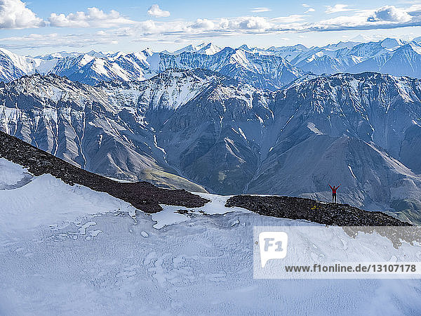 Woman standing with her arm raised while on a ridge line in Kluane National Park and Reserve; Haines Junction  Yukon  Canada