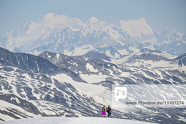 Couple walking on a mountain top with the massive mountains of Kluane National Park and Reserve looming in the distance; Haines Junction  Yukon  Canada