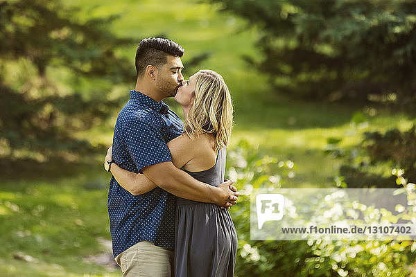 A mixed race married couple stopping to kiss in a city park while they enjoy time together on a warm sunny afternoon; Edmonton  Alberta  Canada
