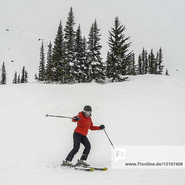 A female downhill skiing and posing for the camera; Whistler  British Columbia  Canada
