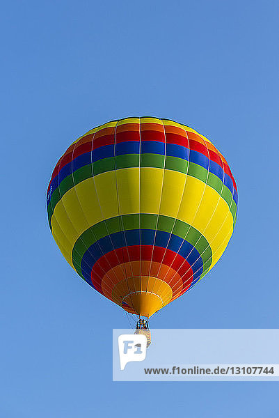 Low angle view of a colourful hot air balloon in a blue sky; St. Jean sur Richelieu  Quebec  Canada