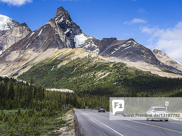 Cars traveling on a road through the rugged Canadian Rocky Mountains in Jasper National Park; Alberta  Canada