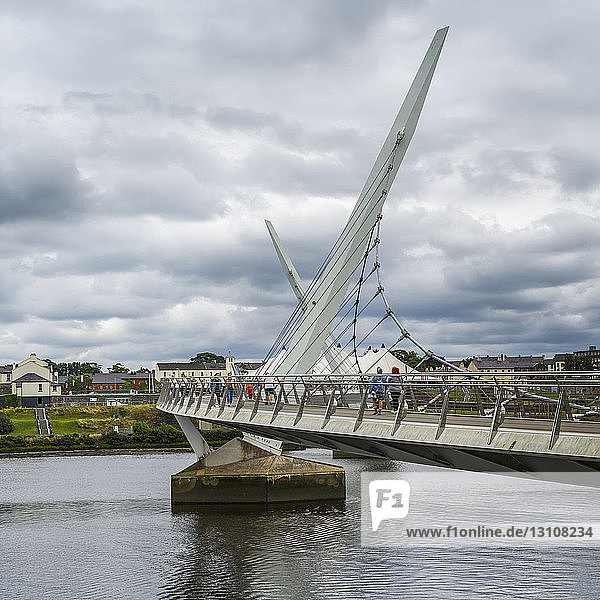Pedestrians on the Peace Bridge  a footbridge crossing the River Foyle  Northern Ireland; Londonderry  Ireland