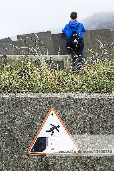 Sign warning of danger on steep cliffs with a pictogram of a tourist falling  Cliffs of Moher; Ennistymon  County Clare  Ireland