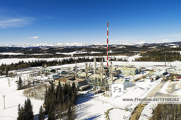 Aerial view of a gas plant in the winter with blue sky  foothills and mountains in the background  South of Bragg Creek; Alberta  Canada
