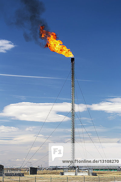 Tall gas plant flare with large fire flare and black smoke and blue sky and clouds in the background; Crossfield  Alberta  Canada