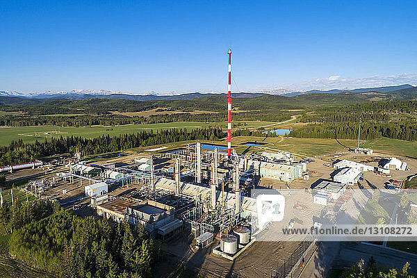 Aerial view of a gas plant in the summer with blue sky  foothills and mountains in the background  South of Bragg Creek; Alberta  Canada