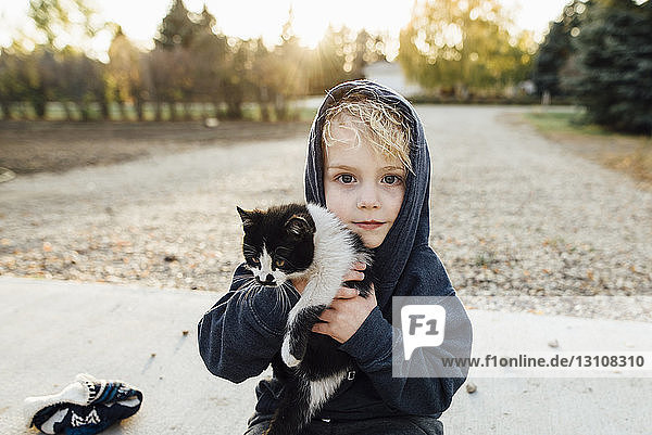Portrait of cute boy carrying cat at park