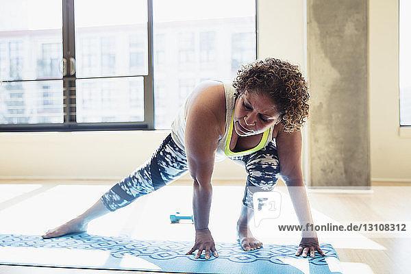 Frau übt Yoga in voller Länge auf Übungsmatte gegen Fenster im Studio