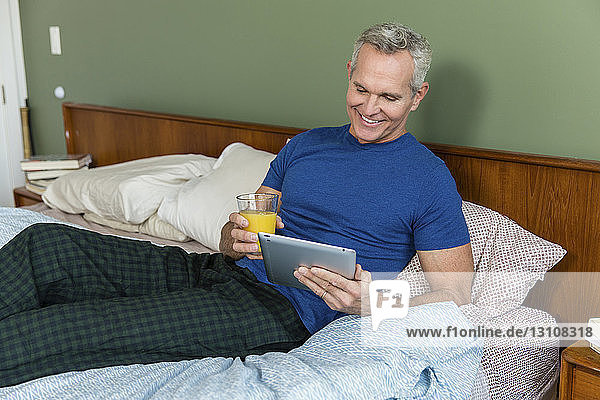 Smiling mature man holding juice while using tablet computer on bed at home