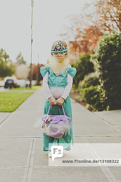 Full length portrait of girl in costume standing on footpath
