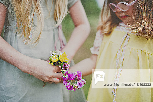 Midsection of sisters holding flowers outdoors