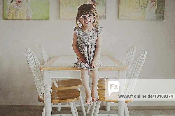 Portrait of cheerful girl sitting on dining table at home