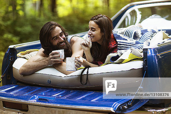 Cheerful couple holding coffee mugs while lying in pick-up truck at forest